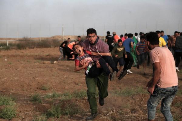 Een gewonde, door Israëlische soldaten beschoten jongen wordt tijdens de Grote Mas van de Terugkeer weggedragen. Een gewonde, door Israëlische soldaten beschoten jongen wordt tijdens de Grote Mas van de Terugkeer weggedragen. ©MOHAMMED ZAANOUN/ACTIVE STILLS/AL JAZEERA