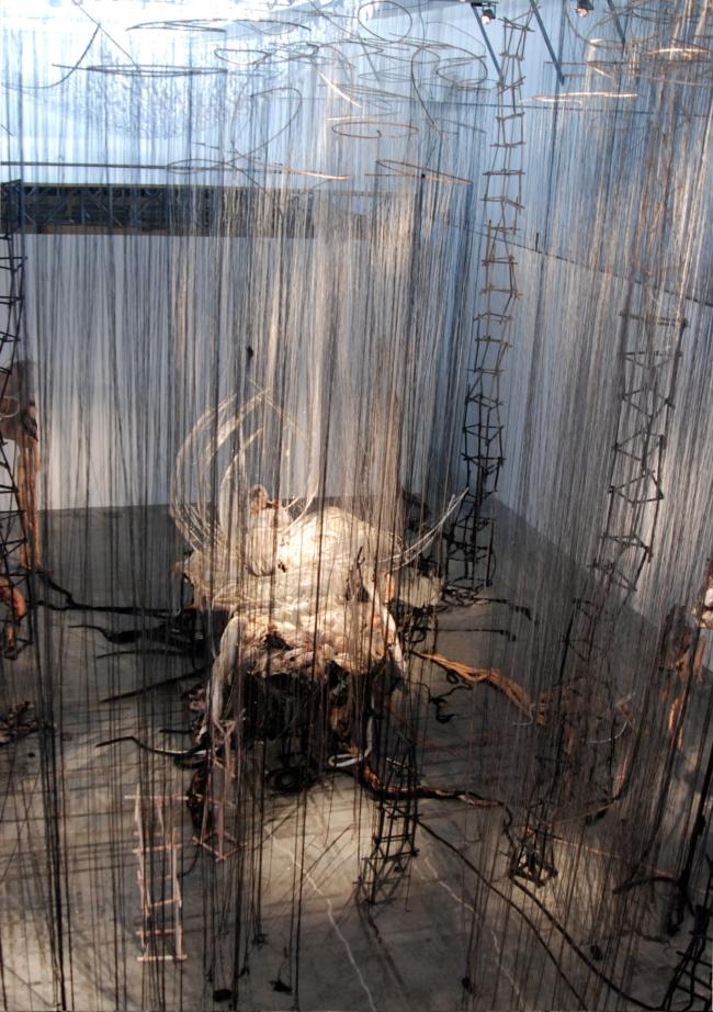 Afbeelding 7. Marya Kazoun in samenwerking met Christian Minotto & Andrea Busetto, Crumbling Desert Castles, in opdracht van Sharjah Biennale 2007, installatie/performance, 11 performers, materiaal: draad, stof, kralen, wol, glas, bamboe, hout, 1200 cm x 1600 cm x 800 cm.