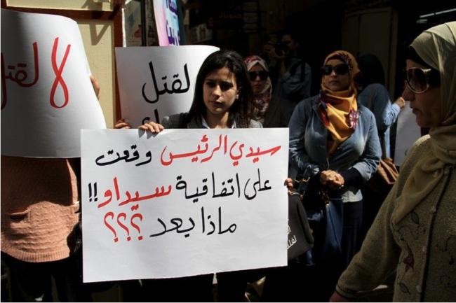 Protest op International Women's Day. De tekst op het bord: 'Meneer de president, u tekende het Verdrag inzake de uitbanning van alle vormen van discriminatie van vrouwen. Wat nu?!'