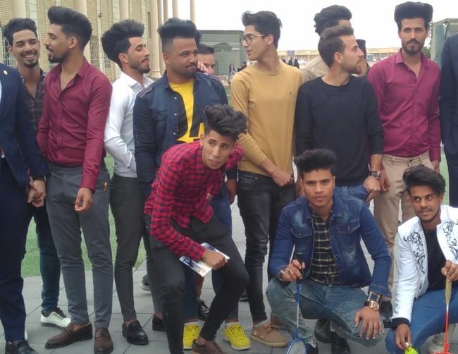 Een groep studenten met typische kapsels uit Bagdad maakt zich klaar voor de foto. Foto: Sylva van Rosse