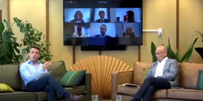 Moderator Mark Snijder (GMOP) en Thijs Berman (directeur NIMD) spreken vanaf de bank. Op de achtergrond vanaf linksboven met de klok mee: Laila al-Zwaini, Ruben Brekelmans, Erwin van Veen, Jeanine Hennis-Plasschaert, Thijs Reuten en Michel Rentenaar